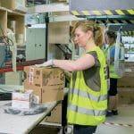 En las mesas de embalaje, los operarios toman los artículos de las bolsas y las embalan según los pedidos.