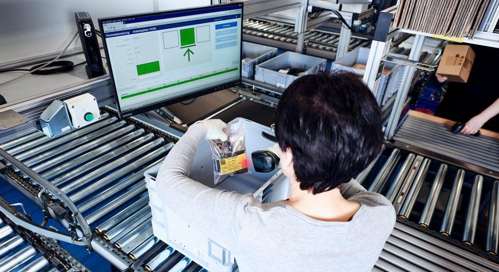 """Vista desde detrás de una empleada que está preparando pedidos en un puesto de trabajo """"mercancía a la persona"""" ergonómico, equipado con una interfaz de usuario easyUse para crear un diseño intuitivo del puesto de trabajo. La mujer toma de una caja de almacenamiento gris un paquete con pequeños materiales electrónicos. En la interfaz de usuario easyUse se indica qué artículo debe tomar y dónde debe depositarlo. Esto aumenta la eficiencia de los procesos de preparación."""