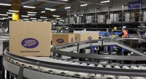 Kartons verschiedener Größen auf einer Fördertechnik in einem Boots-Lager. Nachhaltige Verpackung optimiert Logistik-Prozesse.
