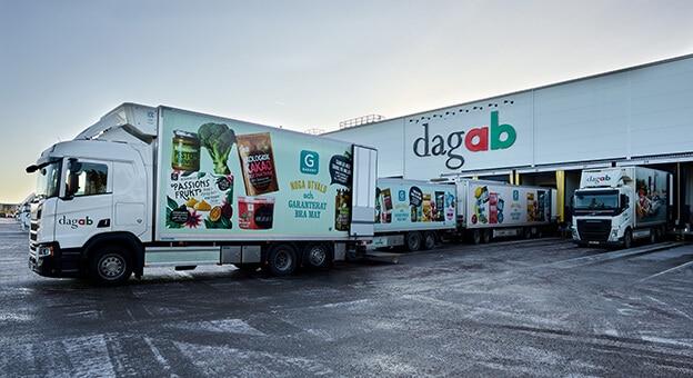 Das Bild zeigt eine Außenaufnahme des Distributionszentrums von Dagab Inköp & Logistik AB, Axfood. Vor dem Lager stehen einige LKW an den Andocktoren, die frische Lebensmittel für die Zustellung an die Filialen abholen. Auf dem Gebäude befindet sich die Aufschrift dagab.