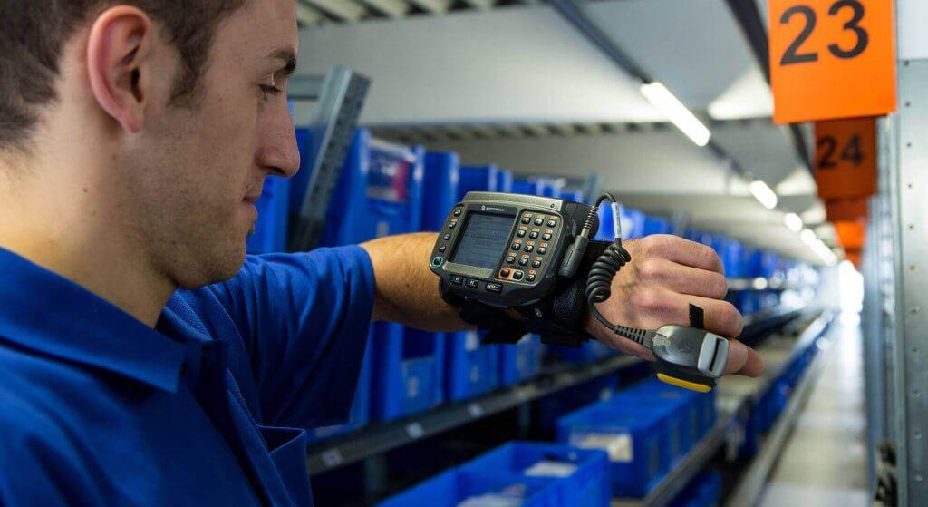 Mitarbeiter blickt auf ein Funkterminal für RF Picking an seinem Arm. Das RF Picking Terminal hilft beim beleglos Kommissionieren und zeigt dem Lagermitarbeiter, wo er welchen Artikel findet.