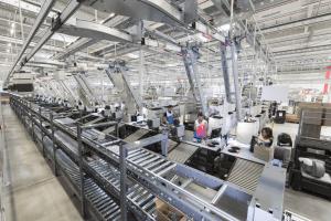 Abgebildet ist eine Halle mit Beladestationen und Packplätzen im Distributionszentrum von Decathlon. An diesen Workstations arbeiten die Mitarbeiter in einer modernen Arbeitsumgebung.