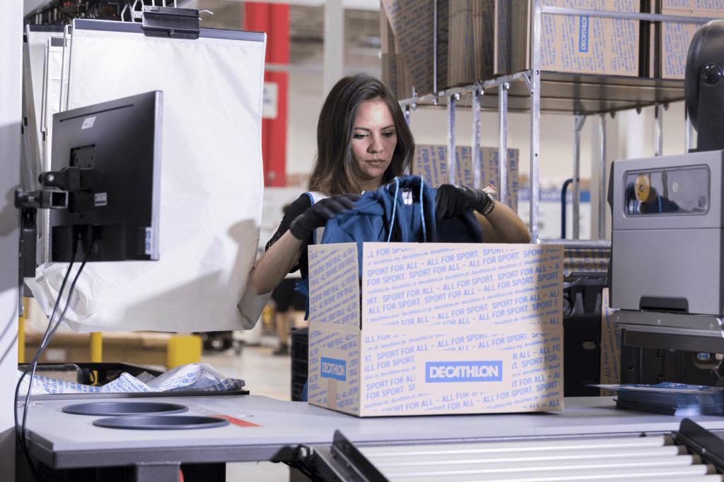 Une collaboratrice dans l'entrepôt logistique de DECATHLON se trouve devant une station manuelle avec des cartons prêts à être expédiés pour des commandes issues de l'e-commerce.