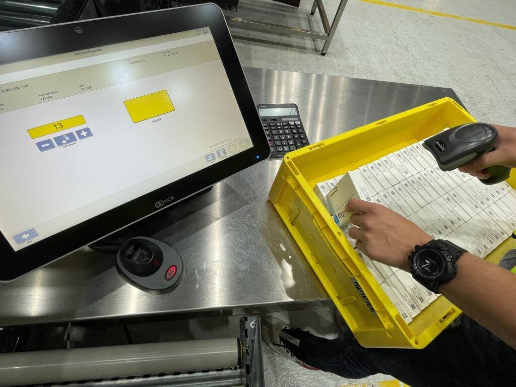 On peut voir un poste de travail dans la zone de l'entrée des marchandises dans un entrepôt pharmaceutique. Un employé scanne les numéros de série des médicaments qui se trouvent dans une caisse jaune à l'aide d'un appareil RF. Sur l'écran situé à côté, l'interface utilisateur basée sur SAP® UI5 affiche l'information correspondant au médicament ainsi que le nombre total de médicaments devant être enregistrés. Outre l'enregistrement de médicaments et de leurs numéros de série, d'autres possibilités de requêtes avec leurs processus telles que la vérification basée sur les risques d'un partenaire non qualifié sont également disponibles dans SAP® EWM by KNAPP au niveau de ces postes de travail.