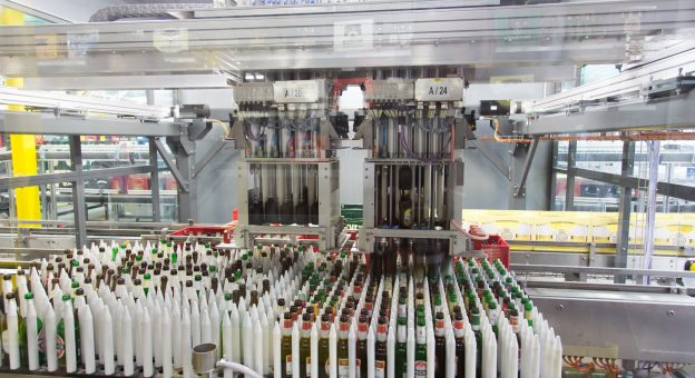 A large number of unsorted single bottles can be seen in the foreground. In the center of the image is a robot with grippers taking single bottles out of beverage crates for sorting.