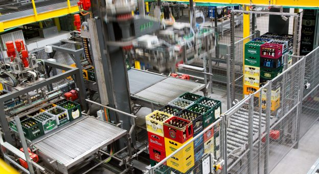 The image is an overview of our sorting system at EDEKA Rhein-Ruhr/t-log. Stacked beverage crates can be seen in the foreground. A robot depalletizes beverage crates layer by layer and transfers them to a conveyor for further processing.