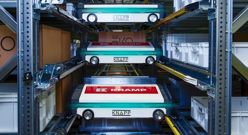 Blick in eine Lagergasse des automatischen Lagersystems OSR Shuttle™ Evo bei KRAMP. Zwei Shuttles sind von vorne zu sehen, ein LED-Streifen zeigt den Status der Shuttles. Das automatische Lagersystem OSR Shuttle™ Evo ist besonders wartungsarm.