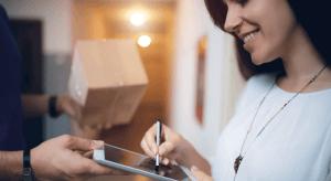 Eine Frau bekommt, die zuvor im Online Shop bestellte Ware. Das Paket wurde ihr nach Hause geliefert und sie unterzeichnet den Lieferschein.