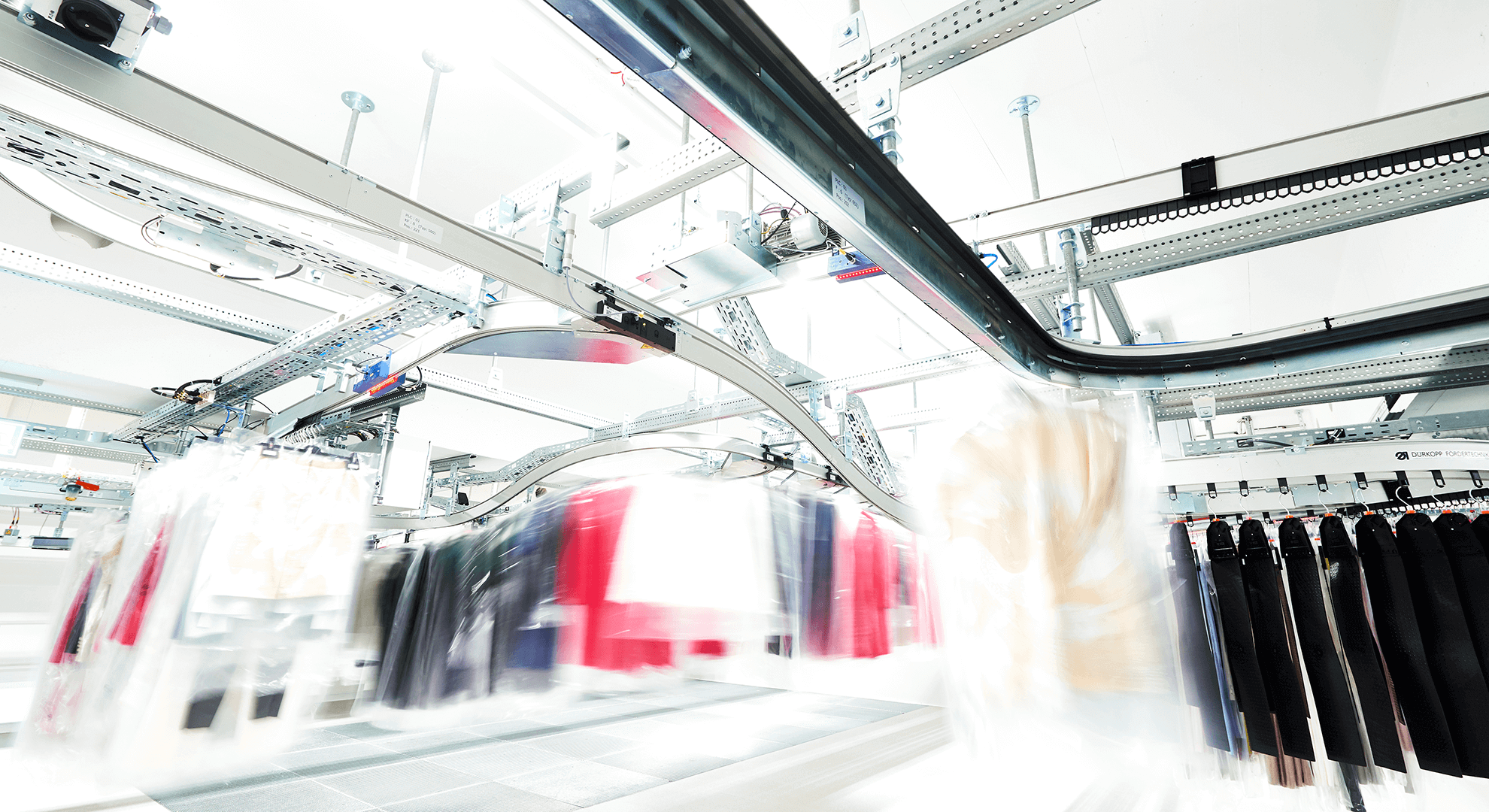 Man sieht eine Halle mit Hängefördertechnik von Dürkopp Fördertechnik in Bewegung mit bunten Kleidungsstücken. Das Hängefördertechnik-System befindet sich im Distributionszentrum für Fashion von Marc Cain.