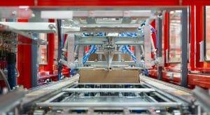 Innenansicht einer Verpackungsmaschine in einem Lager, welche die Kartons auf die richtige Größe für den Inhalt zuschneidet.