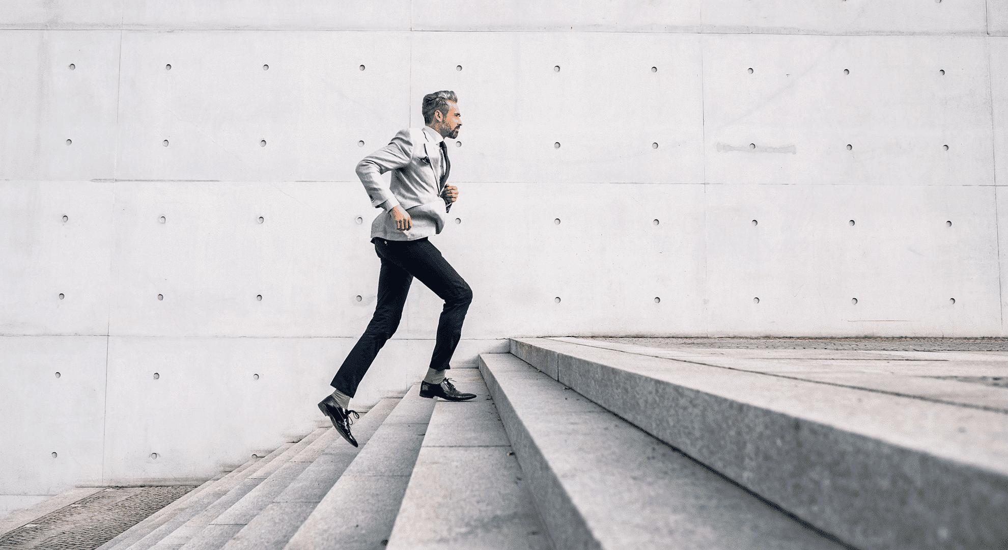 Mann in modernem Fashion-Anzug läuft Treppe hinauf