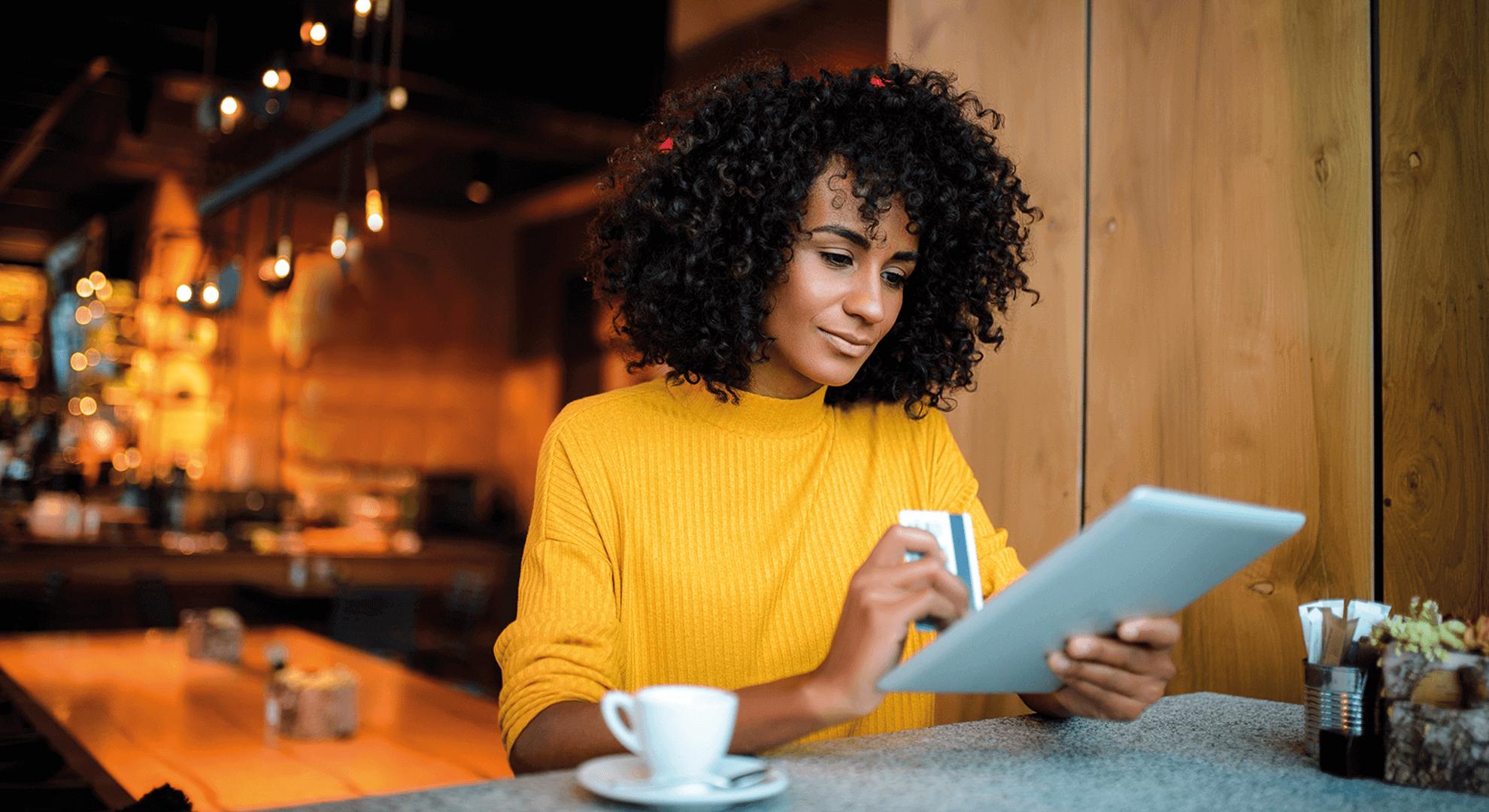 Frau sitzt mit Tablet und Kreditkarte an einer Bar und trinkt einen Kaffee während sie E-Commerce Angebote durchsucht. Damit ihre Bestellung schnell bei ihr ankommt, ist intelligentes E-Com Fulfillment und Automatsierung für E-Commerce gefragt