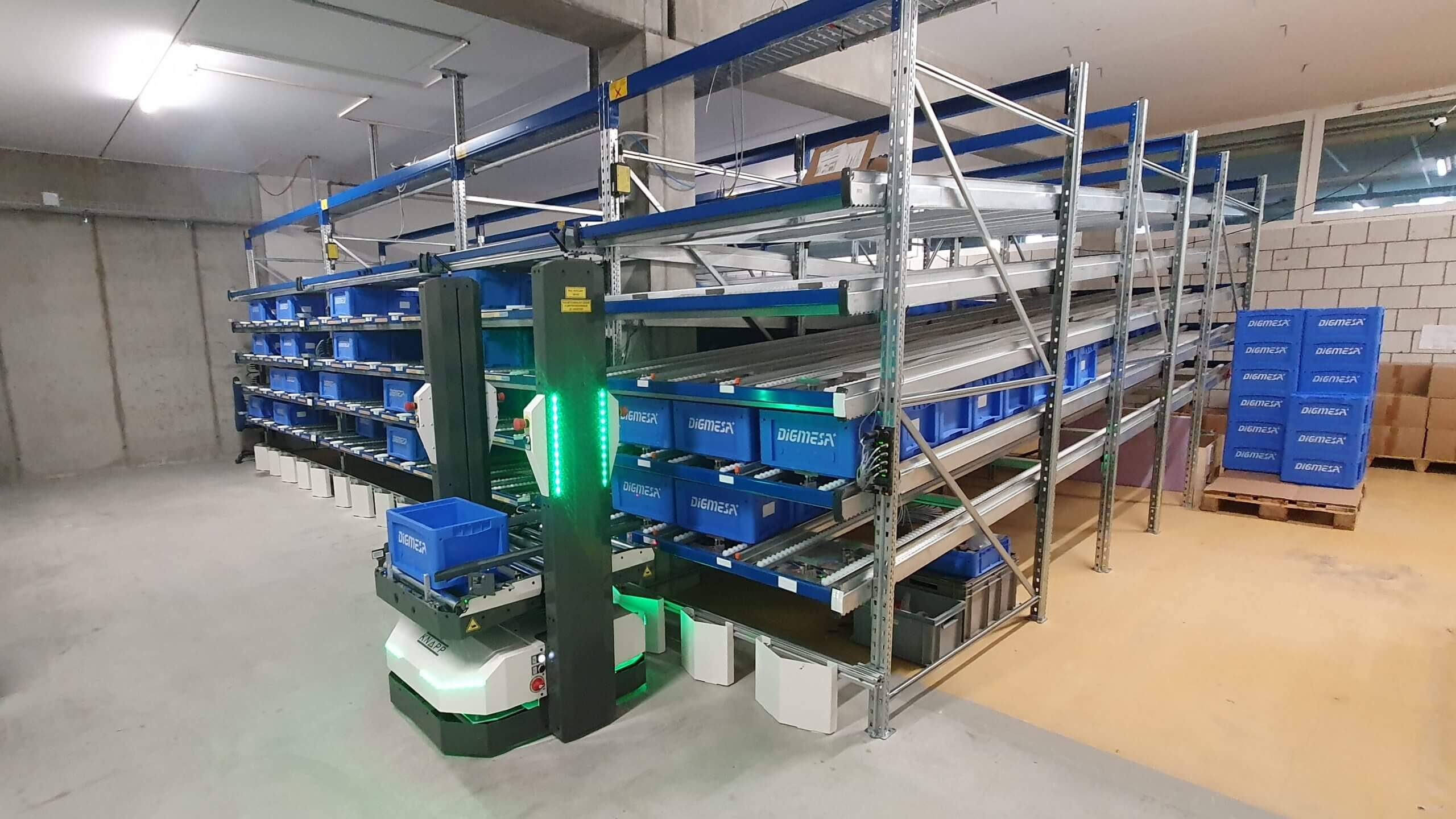 Le véhicule autoguidé (AGV) de KNAPP, appelé Open Shuttle, transfère les conteneurs à un rack de flux.