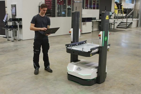 Un empleado instala el sistema de transporte autoguiado de KNAPP de manera rápida y sencilla en la infraestructura existente.