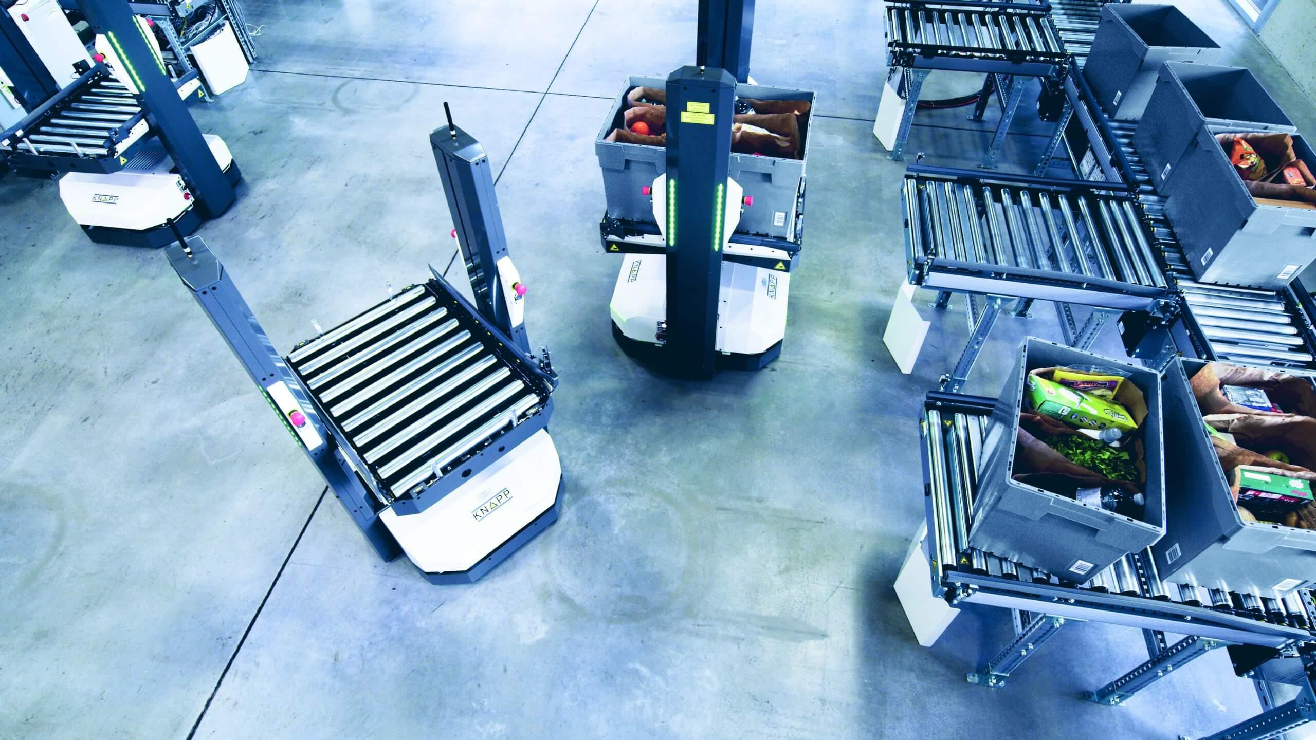Die autonomen mobilen Roboter übernehmen die fertig kommissionierten Aufträge direkt von der Fördertechnik, welche an die Arbeitsplätze angebunden sind.