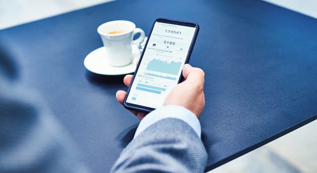 Logistikbetreiber hält Smartphone zur Analyse von Logistik KPIs mit der Software KiSoft Analytics. Zu sehen sind unterschiedliche Dashboards und Daten. Mit KiSoft Analytics behält der den Überblick über die Prozesse und kann die richtigen Entscheidungen für Lager und Supply Chain treffen.