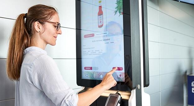 Una mujer se encuentra en un terminal de pedido y selecciona productos con la mano.