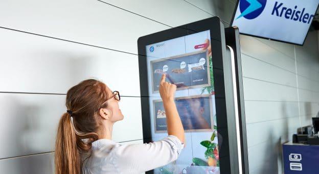 Das Bild zeigt eine junge Frau von hinten, die auf einem großen Screen mithilfe eines Touchdisplays Lebensmittel, die sie kaufen möchte, auswählt und in einen virtuellen Warenkorb legt.