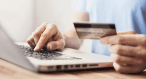 Eine Person sitzt Zuhause vor dem Laptop mit der Kreditkarte, bestellt beim Online Shopping Fashion Produkte mit einem Klick.