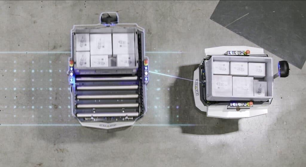Dos robots móviles autónomos Open Shuttle se encuentran en un entorno de almacenamiento. Los robots móviles autónomos (RMA) inteligentes incorporan sensores que les permiten esquivarse mutuamente de forma segura. Cada Open Shuttle transporta una caja de plástico con mercancías. Robots móviles autónomos se encargan del transporte interno de manera fiable.