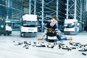 Au centre de l'image se trouve un garçon joyeux qui construit un OSR Shuttle™ avec des briques de Lego noires et blanches. À l'arrière-plan, on peut voir de vrais OSR Shuttle™, autrement dit qui ne sont pas fabriqués en briques de Lego, ainsi qu'un entrepôt à rayonnages en hauteur.
