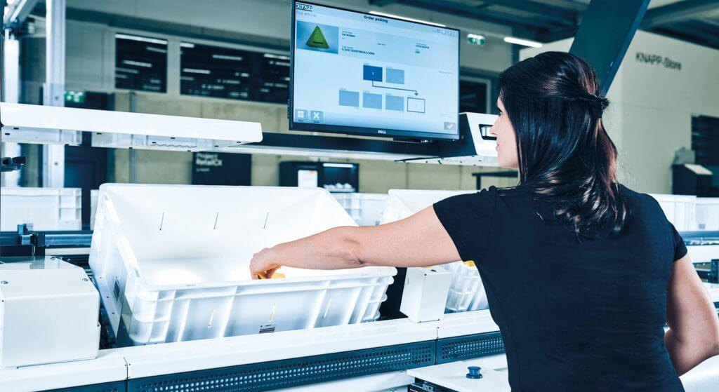 """Una mujer prepara pedidos junto a un puesto de trabajo """"mercancía a la persona"""" ergonómico, el puesto de trabajo Pick-it-Easy de KNAPP, y prepara mercancías desde una caja de plástico. Las mercancías se presentan a la empleada conforme al principio """"mercancía a la persona"""" (GtP). Observa una pantalla táctil que incorpora interfaces de usuario easyUse. Esto simplifica el trabajo en las estaciones de preparación de pedidos y optimiza la calidad y la facilidad de uso. El puesto de preparación Pick-it-Easy mejora la ergonomía para los empleados en el almacén."""