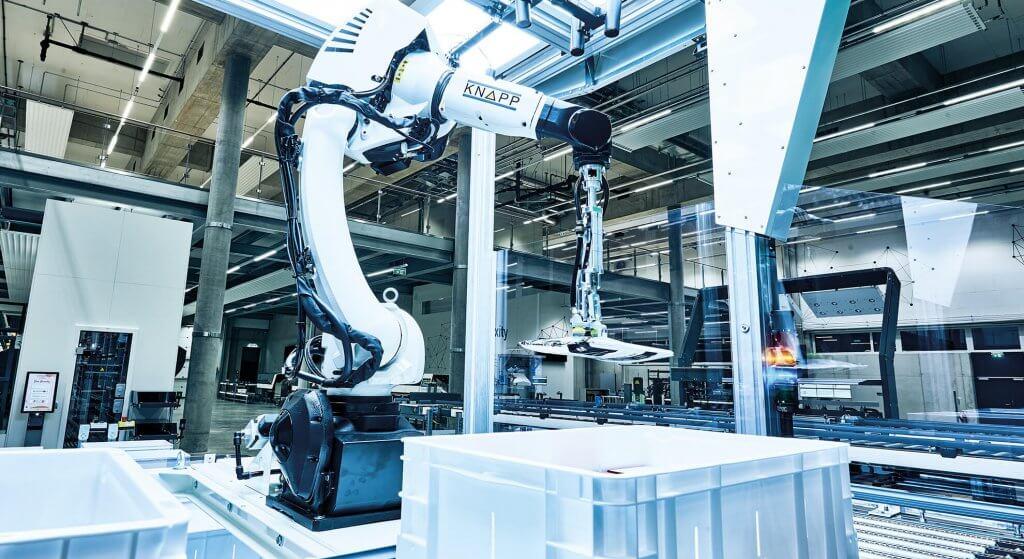 Der Kommissionierroboter Pick-it-Easy Robot in Aktion. Der Roboter zur automatischen Einzelstückkommissionierung entnimmt gerade ein in Folie verschweißtes Hemd aus einem Lagerbehälter. Für einen Roboter ist das eine schwere Aufgabe, der Pick-Roboter Pick-it-Easy Robot meistert das Bin Picking mit künstlicher Intelligenz, dem Covariant Brain.