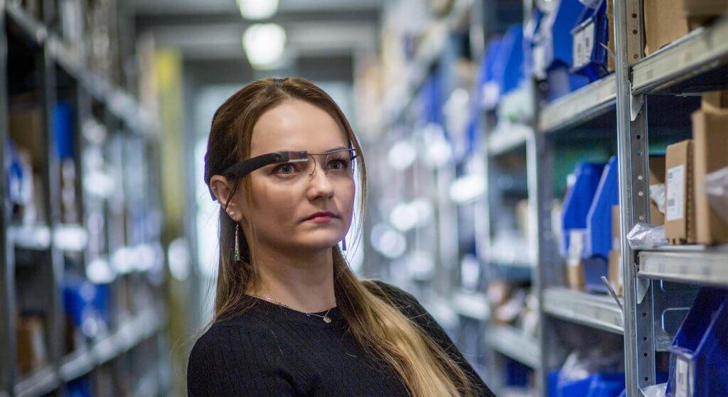 Una mujer con unas gafas KiSoft Pick-it-Smart. Pick-it-Smart es un dispositivo vestible. La tecnología de preparación de pedidos sin uso de documentos facilita la preparación de pedidos. La mujer recibe información importante sobre el pedido, como el emplazamiento de almacenaje, que se muestra directamente en el cristal de las gafas de preparación KiSoft Pick-it-Smart.