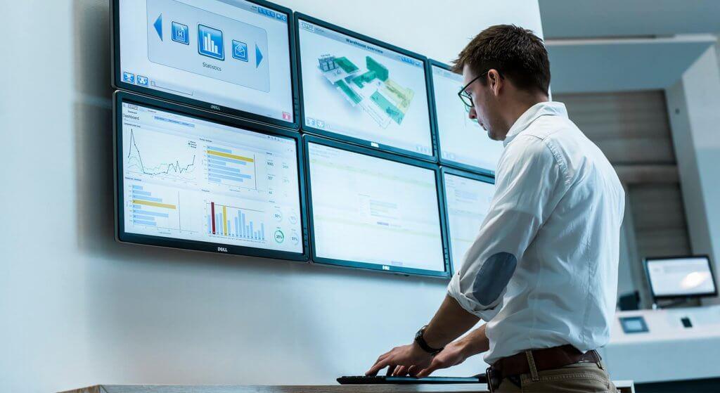 Mann steht vor mehreren Bildschirmen und nutzt mit Maus und Tastatur die Software KiSoft SCADA, die via Schnittstelle mit dem CMMS redPILOT Operational Excellence MAINTENANCE verbunden ist.