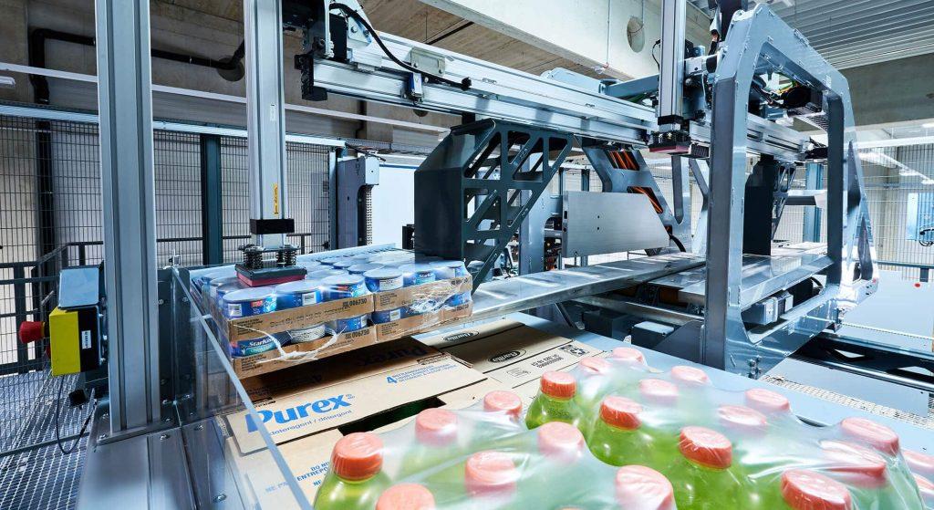 El sistema de preparación de pedidos completamente automatizado RUNPICK toma una unidad de embalaje grande con mercancías y la deposita sobre un palet. RUNPICK—forma abreviada de Robotic Universal Picker— es un robot especialmente desarrollado para el comercio de comestibles. RUNPICK se encarga de la preparación totalmente automatizada de cajas de cartón originales para el comercio de comestibles físico.