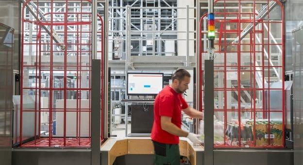 Das Bild zeigt einen ergonomischen Pick-it-Easy Case-Arbeitsplatz. Ein männlicher Mitarbeiter stellt an diesem manuell Aufträge für die Filialbelieferung zusammen.