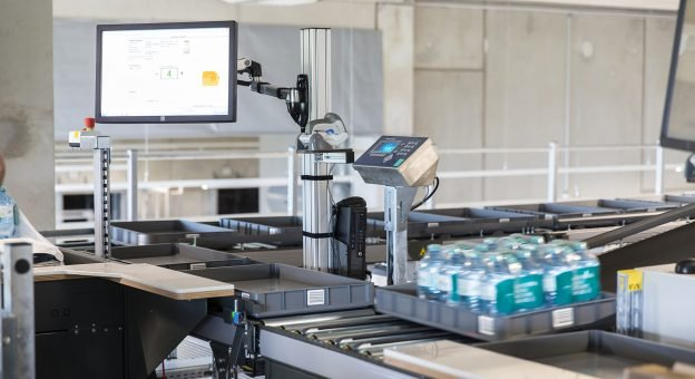 The image shows an ergonomic Pick-it-Easy Case work station with a monitor. The monitor is a visual aid to the employees as they assemble orders. The image also shows a tray with mineral water.