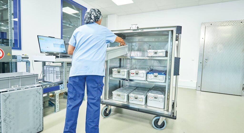 Se ve a un hombre de espaldas laborando en una estación de esterilización del centro de aprovisionamiento sanitario KNAPP.