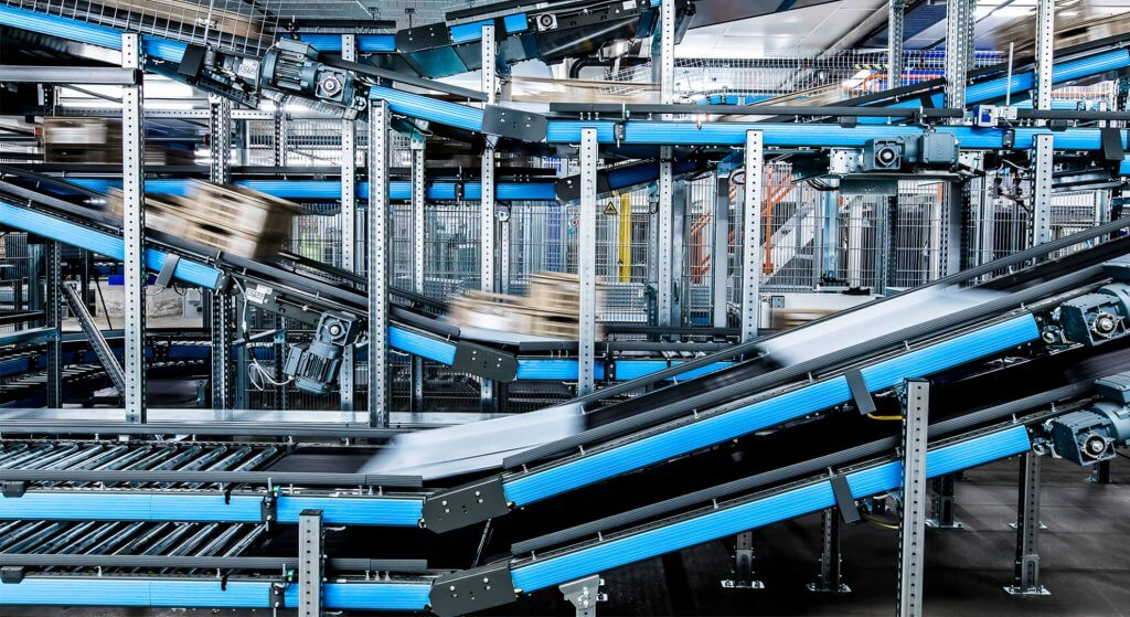 Le système de convoyage universel modulaire Streamline en action chez le client Migros. On voit des marchandises se déplacer à grande vitesse sur les rails du système de convoyage. Il est prévu pour une utilisation polyvalente dans les centres de préparation et de distribution. En tant qu'artère principale dans un système intralogistique, il alimente sans erreur les différentes zones d'entrepôt en marchandises de manière efficace et fiable.