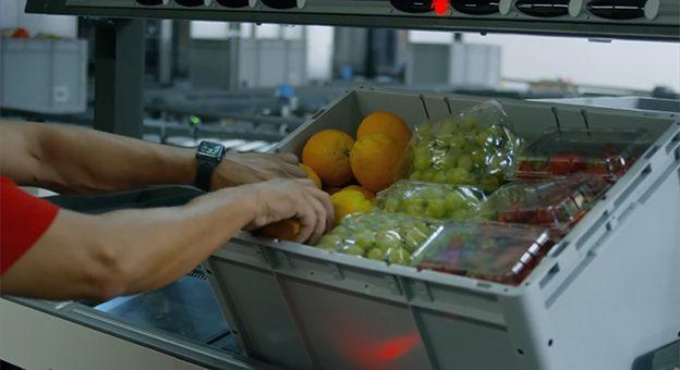 Das Bild zeigt einen Pick-it-Easy-Arbeitsplätzen. Es ist im Detail zu erkennen, wie der Mitarbeiter frische Lebensmittel in Kisten gibt und so E-Commerce-Bestellungen vorbereitet. In der Kiste befinden sich Orangen, Weintrauben und Tomaten.