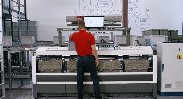 Das Bild zeigt einen Pick-it-Easy-Arbeitsplatz mit einem Mitarbeiter von hinten. Der Mitarbeiter bereitet an diesem ergonomischen Arbeitsplatz E-Commerce-Bestellungen für den Versand vor. Auf einem Screen werden ihm alle Schritte angezeigt, die er bei diesem Prozess durchführen muss. Er erhält dazu genaue Anweisungen, beispielsweise welcher Artikel in welche Tüte zu positionieren ist. Nach der Fertigstellung der Tüten stehen diese für den Versand an die Konsumenten bereit.