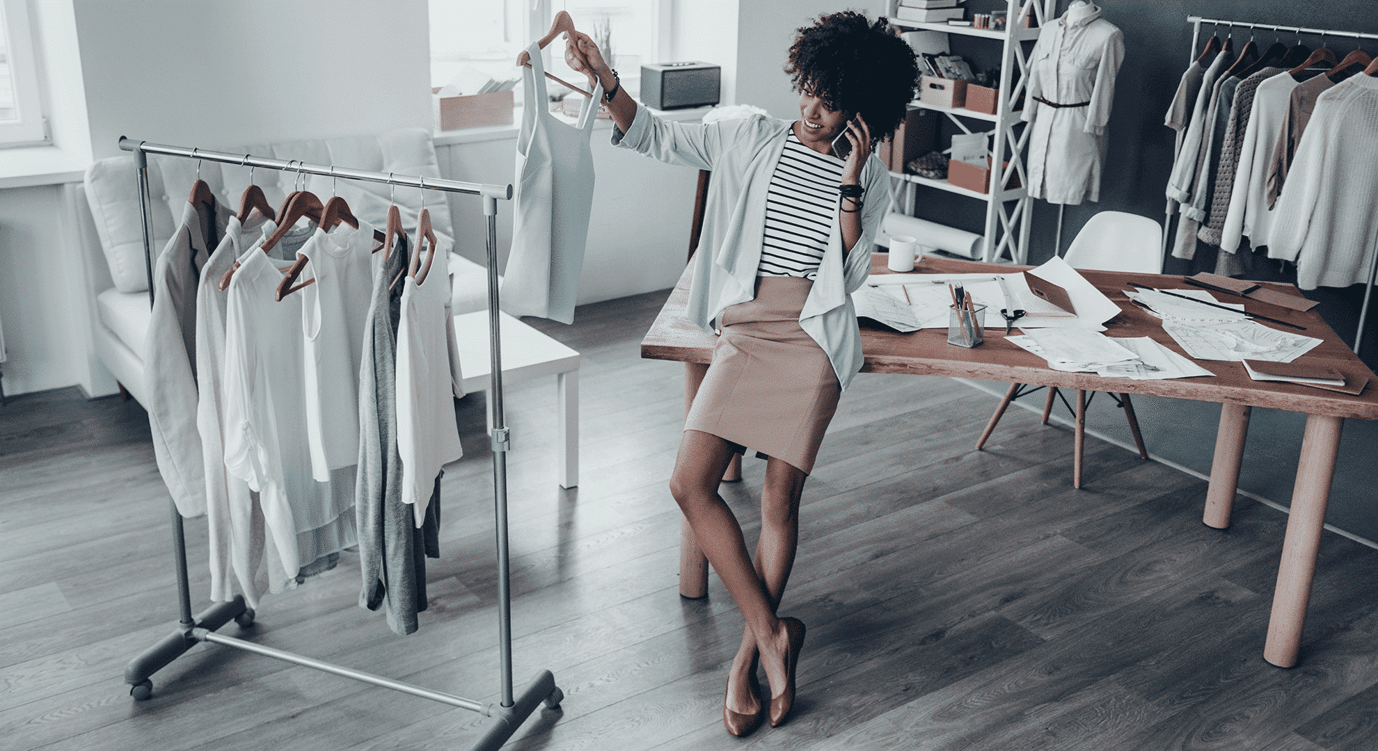 An einem Tisch lehnende, telefonierende Frau wählt das perfekte Oufit von einem Kleiderständer
