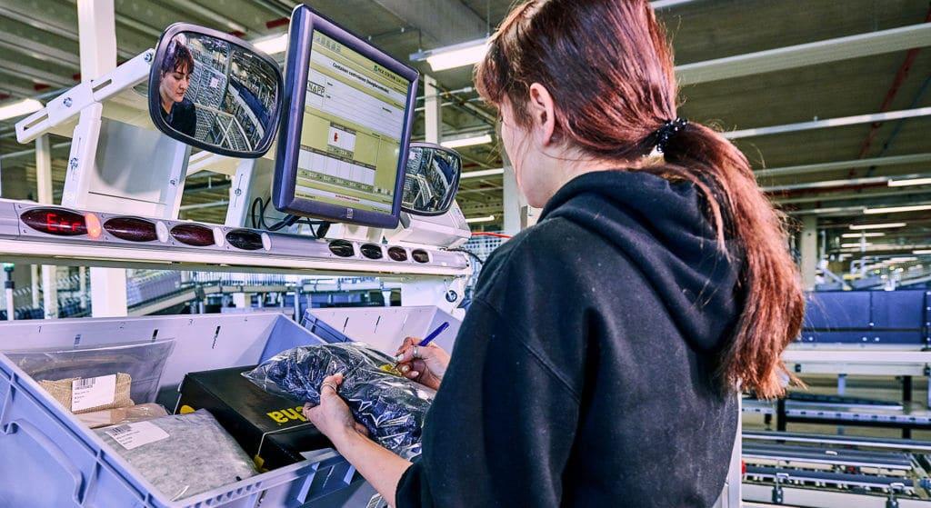 Die Ware-zur-Person-Kommissionierung an den 28 Pick-it-Easy-Arbeitsplätzen ermöglicht ergonomische Auftragsbearbeitung in Bestzeit. Die Mitarbeiter können pro Station 6 Aufträge gleichzeitig bearbeiten.