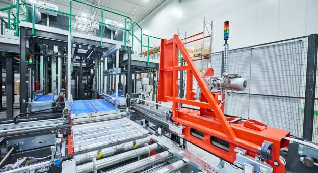 The image shows a fully automatic depalletizing station for the gentle and efficient storing of foods. These robots use a clamping mechanism to separate the containers and place them on the conveyor. These load carriers are automatically transported onwards.