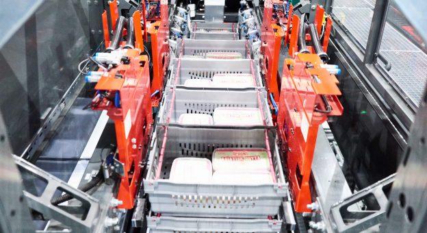 Das Bild zeigt eine vollautomatische Depalettierstation zur artikelschonenden und effizienten Einlagerung der Lebensmittel. Diese Roboter vereinzeln mithilfe von Klemmmechanismen Behälter und geben diese auf die Fördertechnik weiter. Wo diese Gebinde dann automatisch weiter transportiert werden.