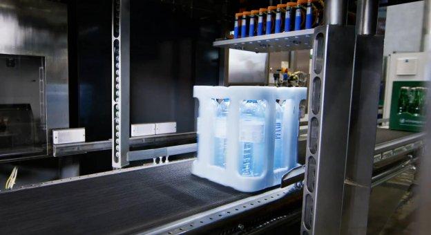 Innenansicht einer Pfandwerterkennungsmaschine. Ein Gebinde in Form einer Getränkekiste mit Vöslauer fährt durch die Erkennungsmaschine. Das Bild zeigt, wie ein Bild von dieser Kiste gemacht wird.