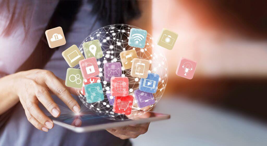 Das Bild zeigt ein mobiles Endgerät, das von einer Frau bedient wird. Die Frau hält das Tablet in ihrer linken Hand und bedient es über den Touchscreen mit ihrer rechten. Rund um das Tablet befinden sich bunte zeichnerische Elemente, die eine durch Daten vernetzte Welt darstellen. Die Zeichen bzw. Icons sind sinnbildlich für die Dienste, die das Internet abgedeckt, wie z.B. Onlineshopping, E-Mail, Orte etc.