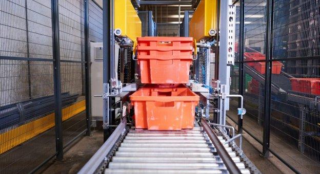 Vorderansicht einer vollautomatischen Entstapelungsmaschine, die TANN-Wannen für Fleisch- und Wurstprodukte vereinzelt. Die Wannen fahren über die Fördertechnik gestapelt in Richtung der Maschine. Klemmen fassen die Gebinde und vereinzeln diese. Die Wannen werden dann einzeln an die Fördertechnik übergeben und Nachfolgeprozessen zugeführt.