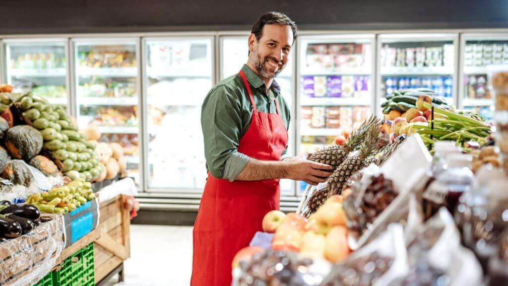 Das Bild zeigt einen männlichen Supermarkt-Mitarbeiter, der die Regale mit frischem Obst befüllt. Sein Blick ist gerade in die Kamera gerichtet und er lächelt freundlich. Seitlich von ihm befinden sich Kisten mit frischem Obst und Gemüse – wie beispielsweise Ananas, Äpfel, Paprika, Auberginen, Gurken, Zucchini und so weiter.
