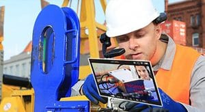 A man with a safety helmet is looking at a tablett. He is talking to a person who is remotely connected with him via a video stream.