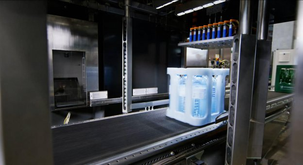 """Inside view of a deposit value recognition machine. A """"Vöslauer"""" water crate passes through the machine. The image shows a picture being taken of this crate."""