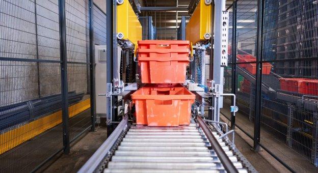 Vista frontal de una máquina desapiladora automatizada que separa bandejas TANN para carnes y productos embutidos. Las bandejas se transportan apiladas a través del sistema de transporte en dirección a la máquina. Dispositivos de apriete sujetan los contenedores y los separan. Las bandejas se entregan individualmente al sistema de transporte para procesos posteriores.