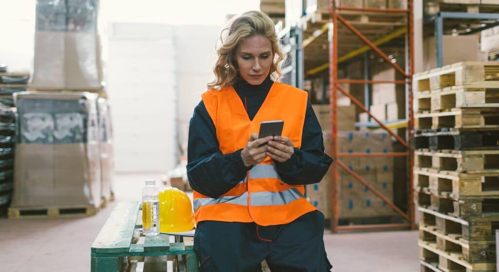 Frau sitzt in einem Lager und nutzt die redPILOT teamAPP auf ihrem Smartphone, eine App zur Schichtplanung in der Operational Excellence Software.