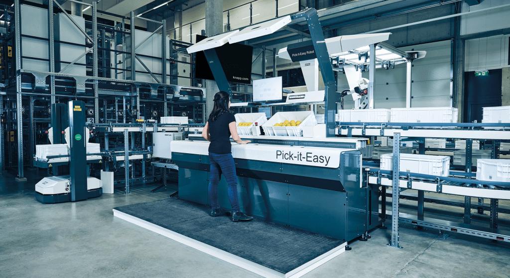 Une femme est debout à coté d'une Pick-it-Easy Work Station, un poste de travail « produit-vers-l'homme ». Le poste de travail « produit-vers-l'homme » convient aux activités manuelles suivantes dans l'entrepôt : préparer les commandes, traiter les retours, effectuer des inventaires, reconditionner et compacter les marchandises ou les services à valeur ajoutée. Derrière le poste de travail Pick-it-Easy se trouvent un robot de prélèvement, un système d'automatisation d'entrepôt ainsi qu'un robot mobile autonome.